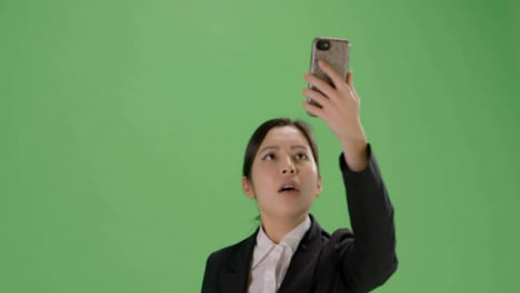 CU-Businesswoman-trying-find-phone-signal-on-green-screen