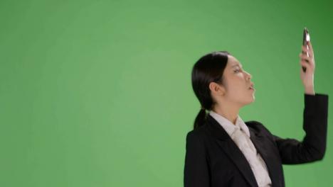 Mujer-de-ángulo-bajo-encontrar-señal-de-teléfono-en-pantalla-verde