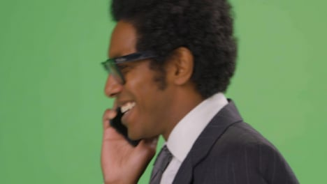 CU-Happy-Businessman-walking-and-talking-on-phone-with-green-screen