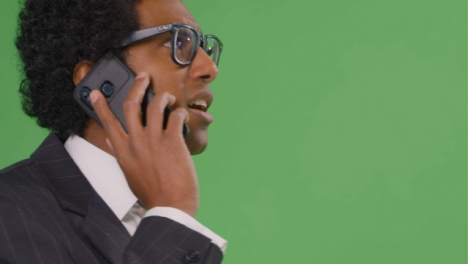CU-Businessman-walking-and-talking-on-phone-with-green-screen