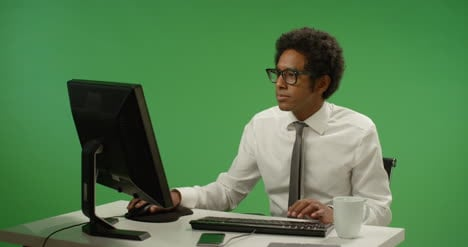 Businessman-sitting-at-desk-typing-on-green-screen