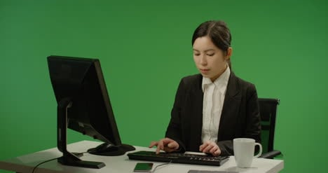 Businesswoman-sitting-at-desk-typing-on-green-screen