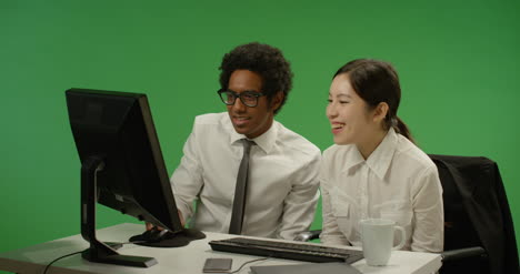 Two-colleagues-look-at-computer-and-smile-on-green-screen