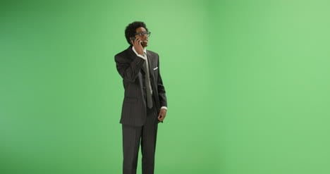 Man-in-suit-talking-on-phone-with-green-screen