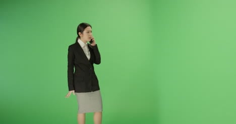 Businesswoman-walking-and-talking-on-phone-with-green-screen