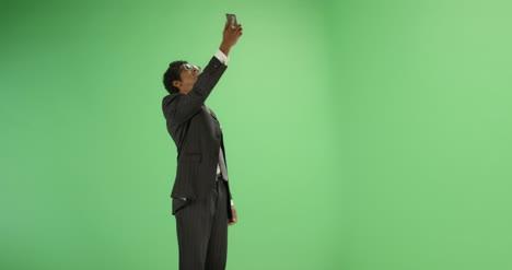 Empresario-encontrar-señal-de-teléfono-en-pantalla-verde