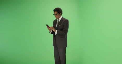 Businessman-takes-out-phone-and-texts-on-green-screen