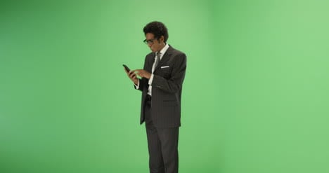 Smiling-man-sending-message-on-phone-with-green-screen