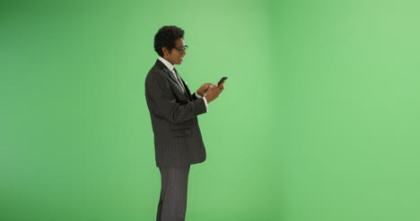 Happy-businessman-typing-on-phone-with-green-screen