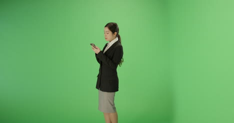 Businesswoman-texting-on-phone-with-green-screen