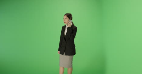 Serious-Businesswoman-answer-phone-on-green-screen