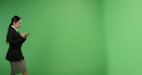 Mensajes-de-texto-de-empresaria-mientras-camina-en-la-pantalla-verde