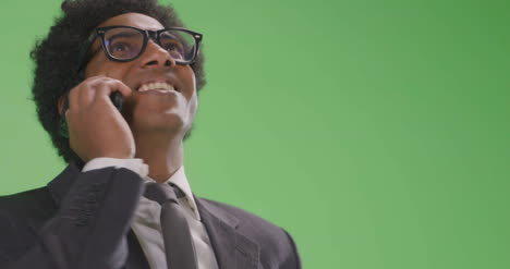 Happy-Businessman-talking-on-phone-on-green-screen-Low-Angle