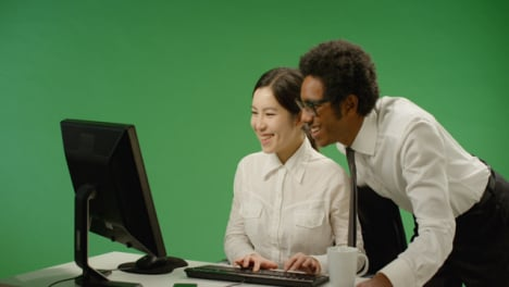 Happy-Businessman-Checking-on-Woman-at-Computer