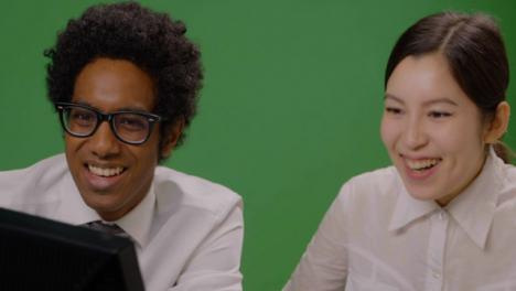 Colegas-de-CU-mirando-computadora-sonriendo-en-pantalla-verde