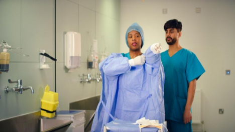 Medical-Staff-Putting-On-Surgical-Gown