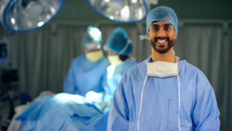 Portrait-of-Smiling-Surgeon-in-Operating-Theatre