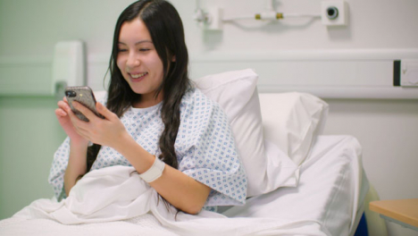 Paciente-del-hospital-femenino-usando-el-teléfono