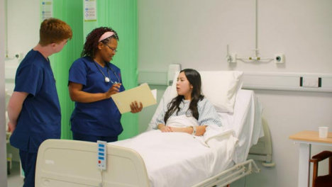 Two-Nurses-Talk-To-Patient-in-Hospital-Bed