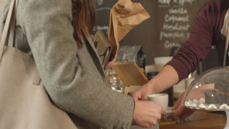 Woman-Being-Served-Coffee-in-Cafe