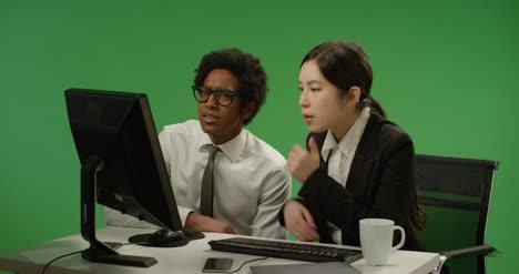 Dos-colegas-parecen-preocupados-por-la-computadora-en-pantalla-verde