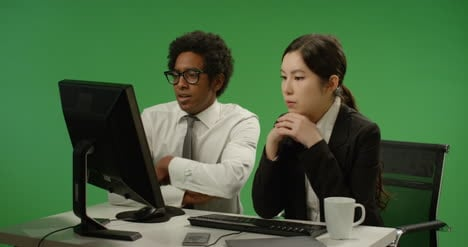 Two-Colleagues-Look-Worried-at-Computer-on-Green-Screen
