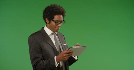 Hombre-de-negocios-usando-tableta-en-pantalla-verde