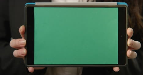 Woman-Holding-Tablet-with-Green-Screen-At-Camera