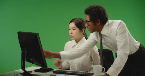 Businessman-Checking-on-Woman-at-Computer