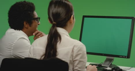 Colleagues-look-at-computer-and-smile-on-green-screen