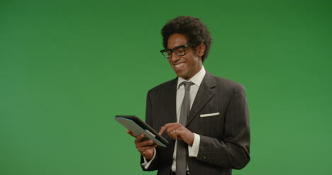 Happy-Businessman-Uses-Tablet-on-Green-Screen