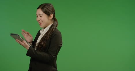Happy-Businesswoman-Uses-Tablet-on-Green-Screen