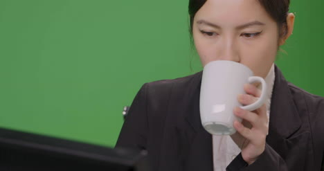 CU-Businesswoman-Sips-Drink-and-Working-on-Computer