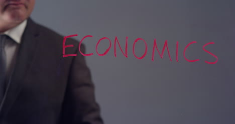 Businessman-Writing-Word-Economics