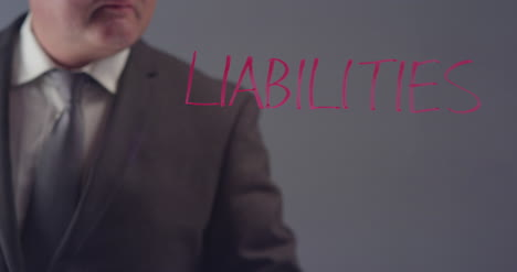 Businessman-Writing-Word-Liabilities