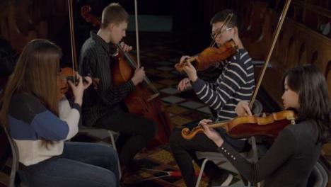 Inclinarse-hacia-abajo-en-el-cuarteto-de-cuerda-tocando-durante-el-ensayo