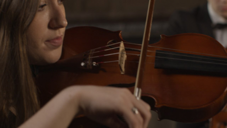 Close-Up-Pan-Of-Female-And-Male-Violinist-During-A-Performance
