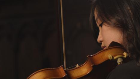 Vista-lateral-de-cerca-violinista-femenina-durante-el-rendimiento