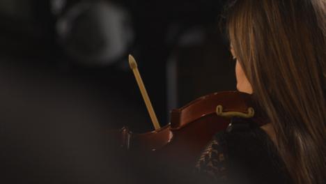 Vista-trasera-Pan-de-violinista-femenina-durante-la-actuación