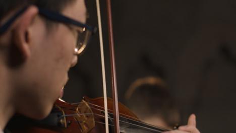 Cerrar-Pan-Up-de-violinista-masculino-durante-la-actuación