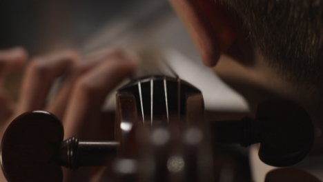 Sobrecarga-cerca-del-violonchelista-masculino-tocando-el-violonchelo