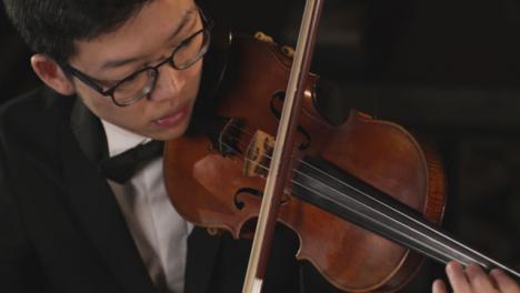 Violinista-masculino-tocando-el-violín-durante-una-actuación