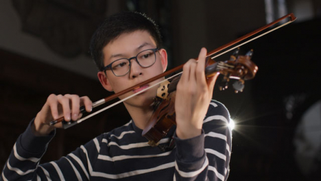 Vista-frontal-de-cerca-violinista-masculino-tocando