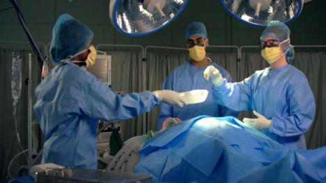 Assistentin-Die-Dem-Chirurgen-Ein-Chirurgisches-Instrument-übergibt