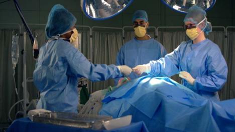 Arzthelferin-Die-Dem-Chirurgen-Ein-Chirurgisches-Instrument-übergibt