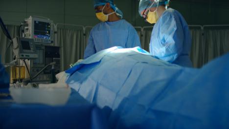 Pan-Medical-Staff-Look-at-Monitor-During-Surgery