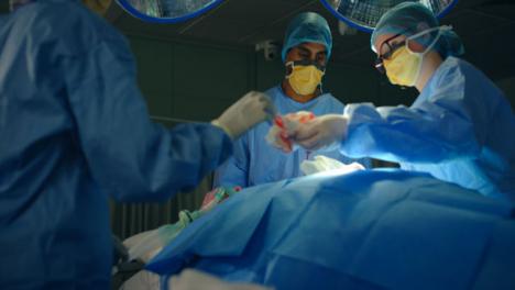 Pan-Asistente-Médico-Pasando-Una-Gasa-Al-Cirujano-Low-Key