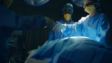 Pan-Arzthelferin-übergibt-Skalpell-An-Chirurgen-Zurückhaltend