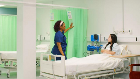 Female-Nurse-Opens-Curtain-Talking-to-Patient