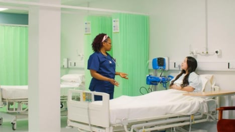 Female-Nurse-Chatting-to-Patient-in-Hospital-Bed